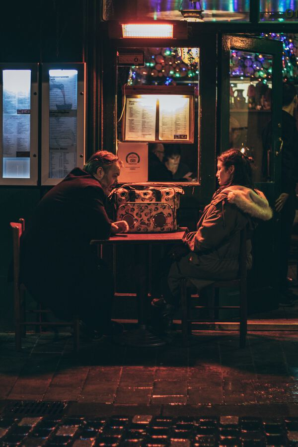 Couple talking at a table in a dimly lit restaurant